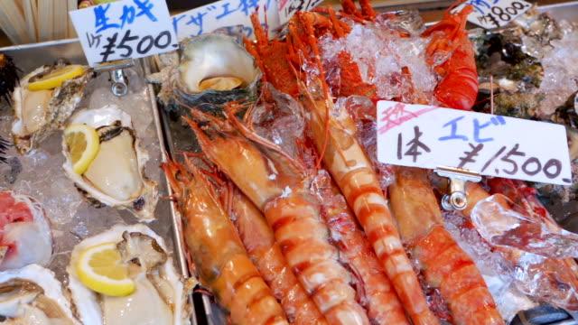 vídeos de stock e filmes b-roll de panning retail display of seafood in fish market, japan. - captura de peixe