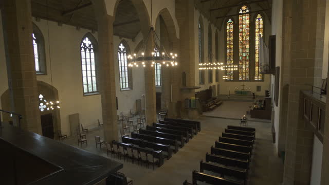 panning reveal from the balcony of the full interior length of an old german church with soaring stained glass windows, pews, vaulted ceiling, and stone carvings - erfurt, germany - apse stock videos & royalty-free footage