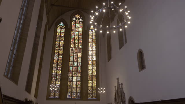 panning reveal past a statue to reveal a wall of soaring stained glass windows in the interior of an old german church - erfurt, germany - apse stock videos & royalty-free footage