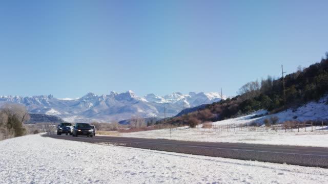 晴れた青い空の下で晴れた日にコロラド州ユーレイの冬外でロッキー山脈の雪に覆われたサンファン山脈麓に沿って運転車の流し撮りを明らかに - ユアレイ市点の映像素材/bロール