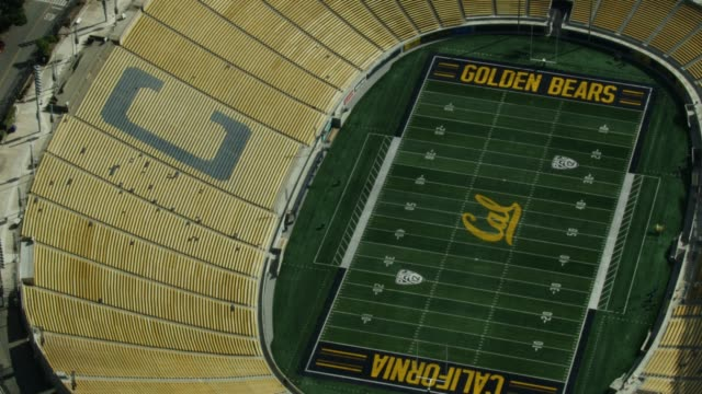 Panning right shot from the grandstand seats forming a letter C to the football field of the California Memorial Stadium