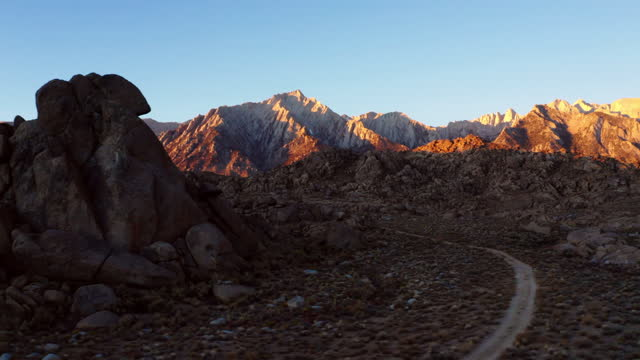 panning right through rock formations with rugged mountain peaks, dramatic sunlight, clear blue sky, and rocky terrain - sierra, california - californian sierra nevada stock videos & royalty-free footage