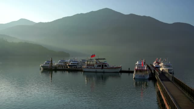 panning right to chaowu pier with sunlight reflection on the lake, sun moon lake, taiwan - sun moon lake stock videos and b-roll footage