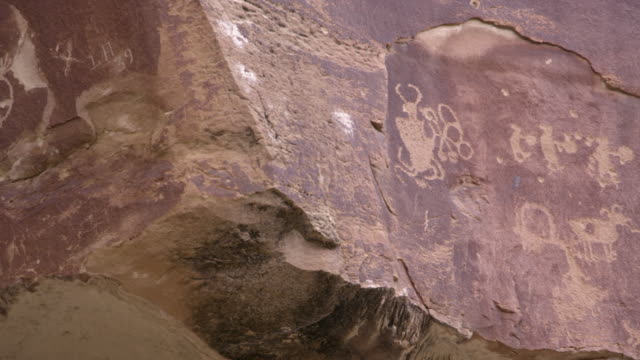 vídeos de stock e filmes b-roll de panning rock with carvings of various petroglyphs from native americans - anasazi