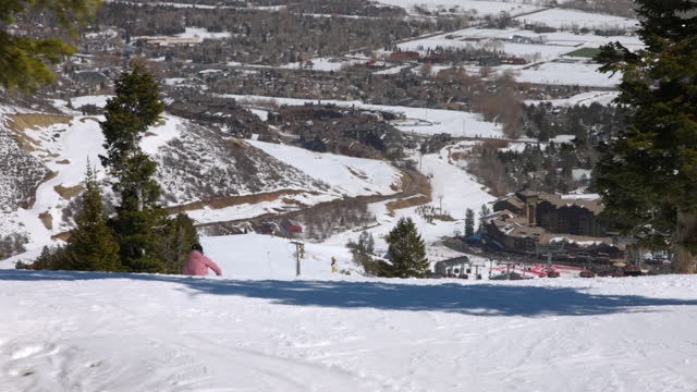 panning scenic shot of people skiing on snowy mountains during sunny day - park city, utah - park city stock videos & royalty-free footage