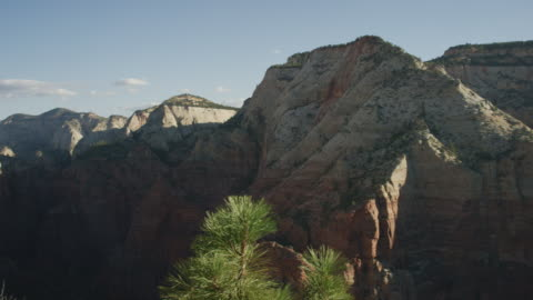 panning scenic shot revealing woman sitting on edge of a cliff - canyon stock videos & royalty-free footage