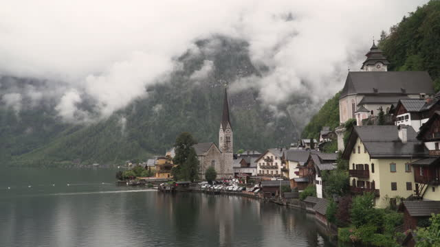 panning scenic view of famous hallstatt mountain village and boat port on bad weather condition, a rainy day in summer covering much cloudy. one of the travel destinations in austrian culture and the european alps and lakeshore in europe - austrian culture stock videos & royalty-free footage