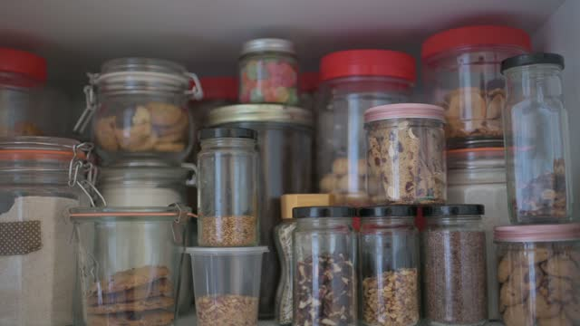 panning shoot showing food storage in shelf cabinet in kitchen biscuit, seed, raw food, preserved food, dried food and flour in jar and plastic container - storage compartment stock videos & royalty-free footage