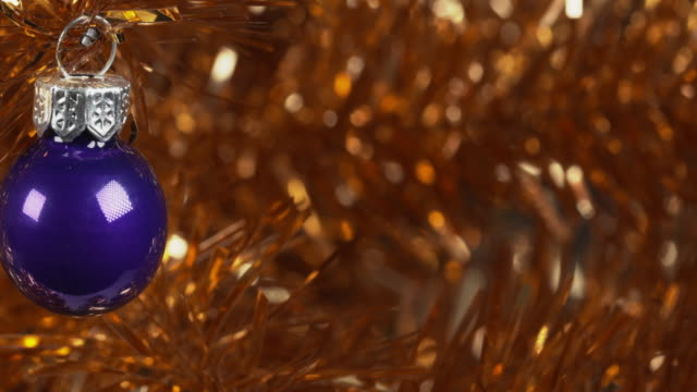 panning shot across a blue ornament hanging from a gold christmas tree. - tinsel stock videos & royalty-free footage