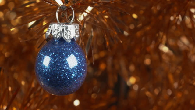 panning shot across a gold tinsel tree to a blue glitter christmas bauble. - tinsel stock videos & royalty-free footage