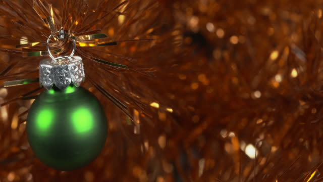 panning shot across a green bauble decorating a gold christmas tree. - tinsel stock videos & royalty-free footage