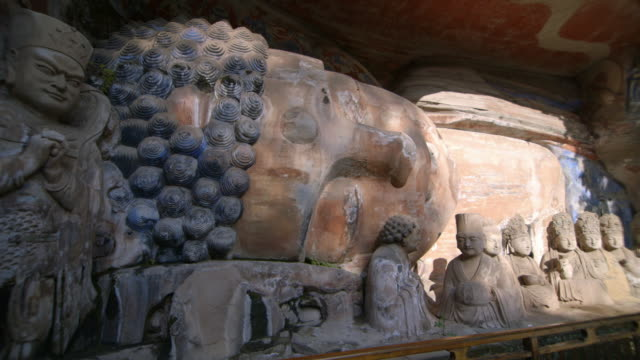 panning shot across a large reclining buddha statue at the dazu rock carvings in china.  - buddha stock-videos und b-roll-filmmaterial