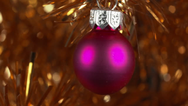 panning shot across a pink bauble decorating a gold christmas tree. - tinsel stock videos & royalty-free footage