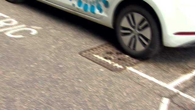 Panning shot across a road and parking spot marked 'Electric Vehicles Only'