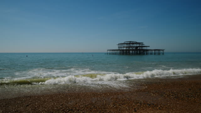 panning shot across brighton beach from the west pier to the palace pier. - brighton brighton and hove stock-videos und b-roll-filmmaterial