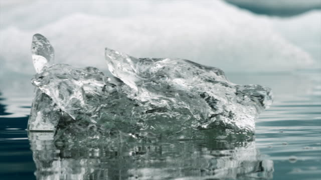 vídeos de stock, filmes e b-roll de panning shot across crystal clear lumps of ice floating on a lake in iceland. - ice crystal