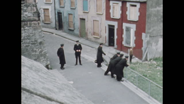 panning shot across londonderry skyline to police as they wait for the apprentice boys parade; august 1969. - panning stock videos & royalty-free footage