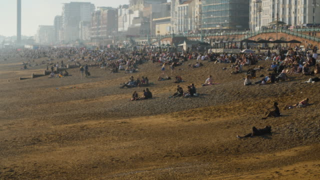 panning shot across people relaxing and enjoying the sunny weather on brighton beach, uk. - brighton brighton and hove stock-videos und b-roll-filmmaterial