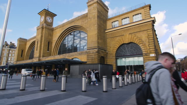 Panning shot across the front exterior of Kings Cross Station, London.
