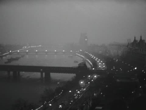 panning shot across the river thames at night to the royal festival hall. 1960. - ロイヤルフェスティバルホール点の映像素材/bロール