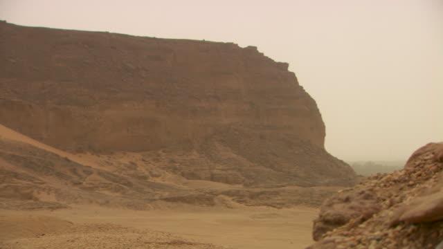 vídeos de stock, filmes e b-roll de panning shot across the sacred mountain of jebel barkal at nuri in sudan. - sudão