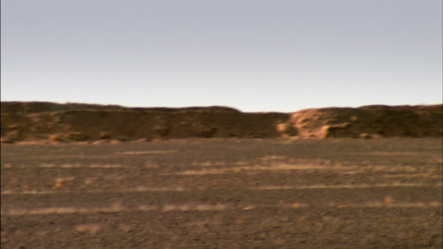 Panning shot across the stone berm that separates Moroccan controlled Western Sahara from the Polisario Front controlled area.