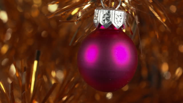 panning shot across various baubles decorating a gold christmas tree. - tinsel stock videos & royalty-free footage