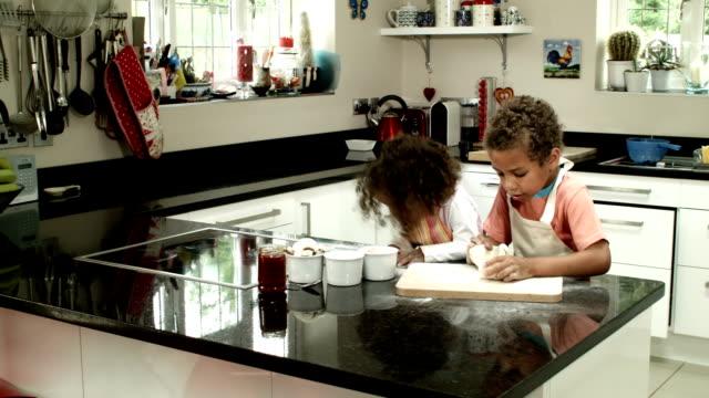 vídeos de stock, filmes e b-roll de panning foto hd: biracial menino e menina rolando massa - rolo de pastel
