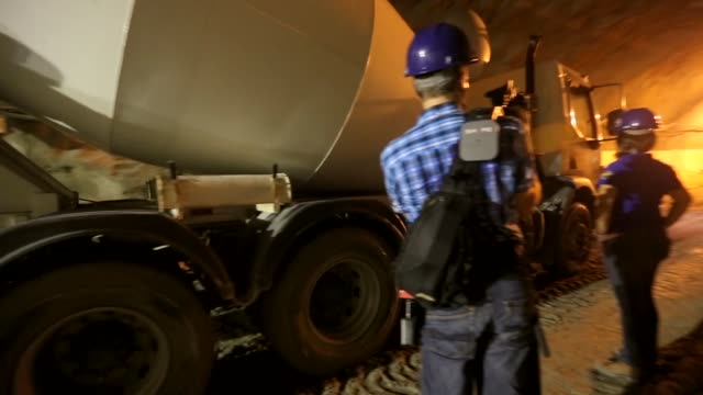 panning shot, concrete mixer truck driving in a tunnel. workers construct a tunnel as part of ongoing upgrades to the port district ahead of the 2014... - ゴールを狙う点の映像素材/bロール