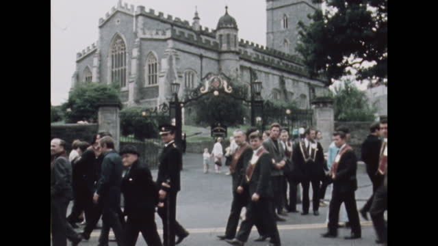 panning shot down from st columb's cathedral to people celebrating the apprentice boys parade in londonderry, northern ireland; 1969. - panning stock videos & royalty-free footage