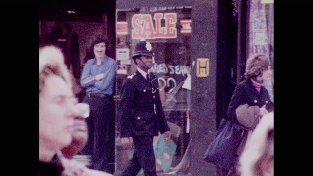 panning shot following policeman in uniform walking along busy streets amongst the community in lewisham, london; 1973. - capital cities stock videos & royalty-free footage