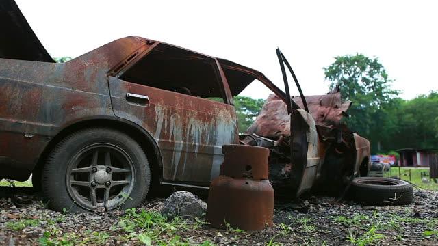 panning schuss für abgestürzt, zerstörten und verlassenen auto links neben der seite der landstraße ausgebrannt. - zurückgelassen stock-videos und b-roll-filmmaterial