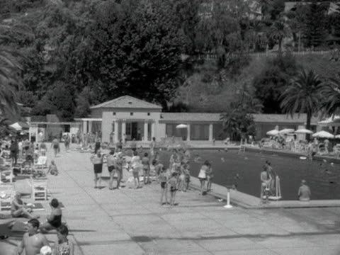 Panning shot from an open air swimming pool to the beach at Monte Carlo 1950s
