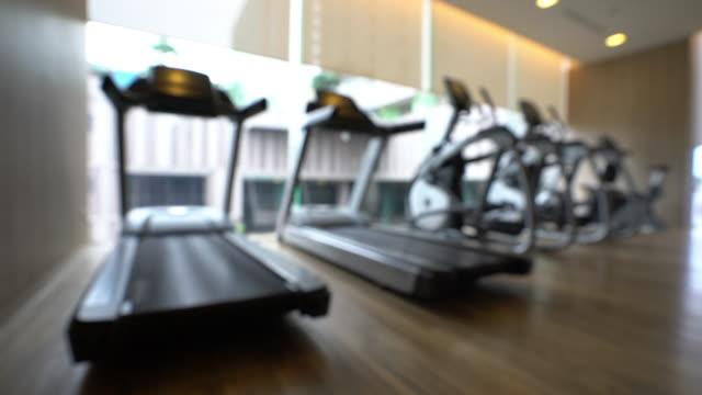 panning shot: gym hintergrund in fitness center - trainingsraum wohnraum stock-videos und b-roll-filmmaterial