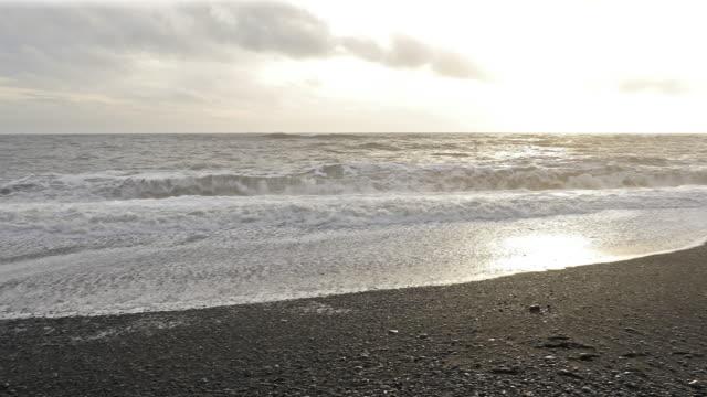 panning shot huge wave at black beach vik iceland - dyrholaey stock videos & royalty-free footage