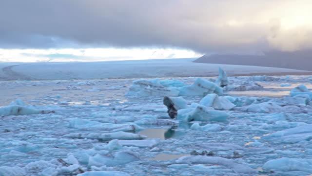 vídeos y material grabado en eventos de stock de panning shot: jokulsarlon laguna y glaciar vatnajokull islandia - helado condición