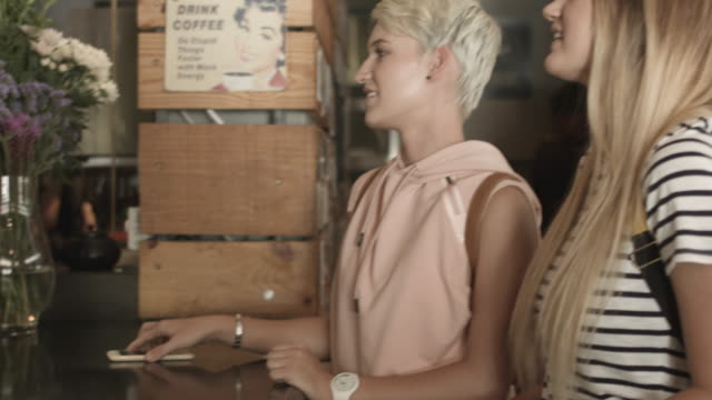 vídeos de stock e filmes b-roll de panning shot, lesbian couple get coffee - cabelo curto comprimento de cabelo