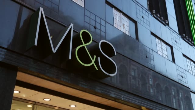vídeos de stock e filmes b-roll de panning shot marks and spencer logo members of the public walk past a branch of marks spencer on oxford street on january 7 2014 in london england... - marks and spencer