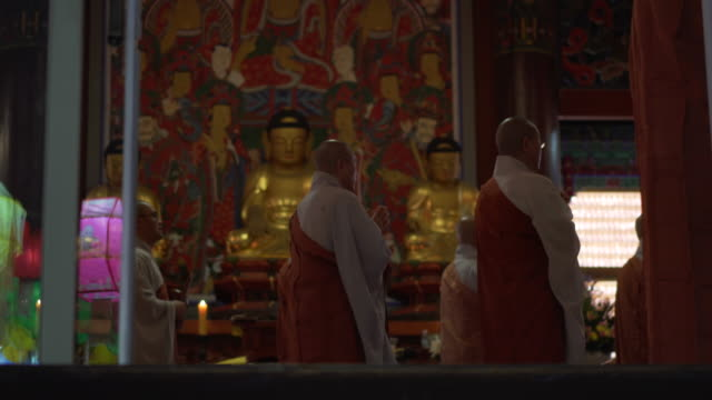 panning shot, monks pray in temple - buddhismus stock-videos und b-roll-filmmaterial