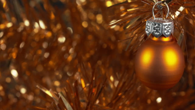 panning shot moving over a gold ornament hanging from a tinsel christmas tree. - tinsel stock videos & royalty-free footage