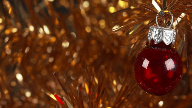 panning shot moving over a red ornament hanging from a tinsel christmas tree. - christmas tree stock videos & royalty-free footage