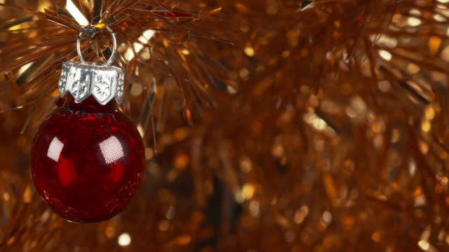 panning shot moving over a red ornament hanging from a tinsel christmas tree. - tinsel stock videos & royalty-free footage
