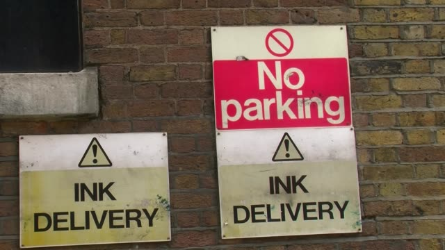"""panning shot, """"no parking! ink delivery"""" sign outside of former news of the world offices. news of the world office exterior in wapping, london on... - no parking sign stock videos & royalty-free footage"""