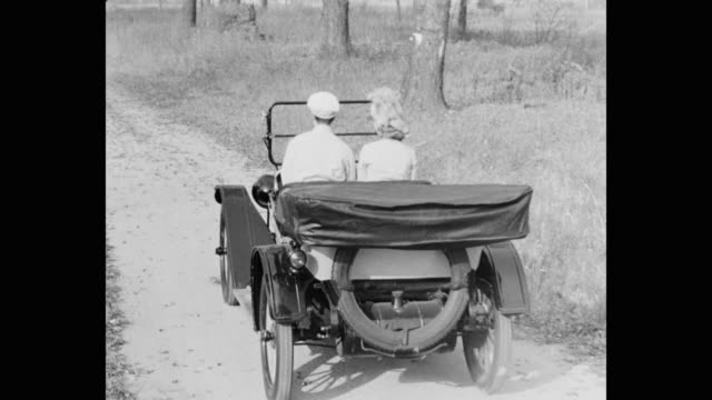 panning shot of 1910's couple driving vintage car on country road - 1920 video stock e b–roll