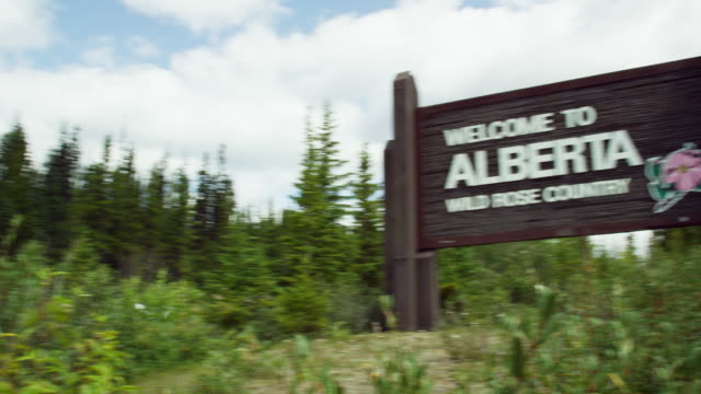 "panning shot of a car driving along a road on the united states/canadian border into alberta with the ""welcome to alberta, wild rose country"" sign by the side of the road surrounded by forest on a partly cloudy day - montagne rocciose video stock e b–roll"