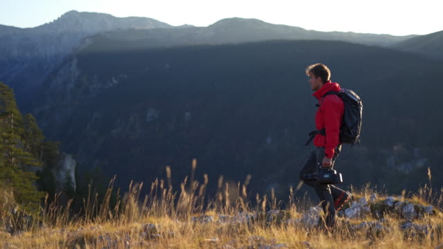 panning shot of a filmmaker on a mountain cliff near sunset - film director stock videos and b-roll footage