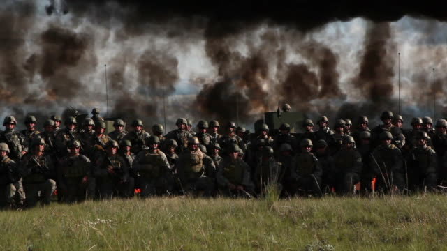 panning shot of a group of soldiers lined up with explosion behind.  - military training stock videos & royalty-free footage