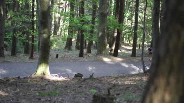 schwenkschuss einer bergstraße mit vorbeifahren von bäumen und radfahrer - exploration stock-videos und b-roll-filmmaterial