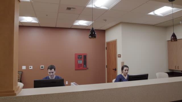 vídeos de stock, filmes e b-roll de panning shot of a receptionist leaving a front desk - escrivaninha
