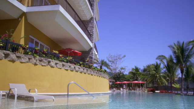 panning shot of a resort building to an outdoor pool. - costa rica video stock e b–roll